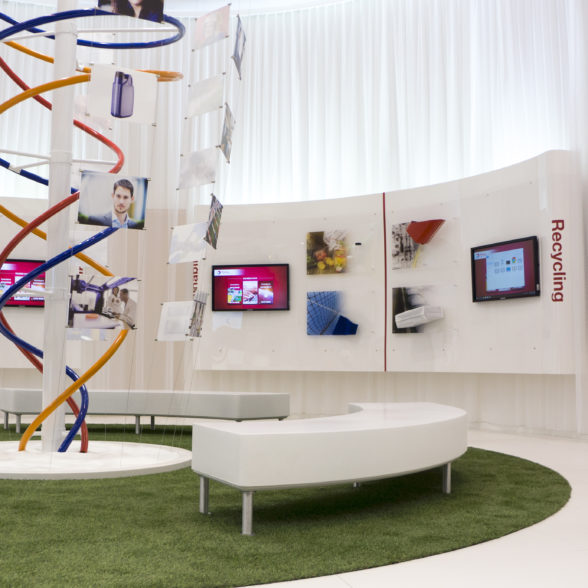 A centrally positioned Helix inspired on the chemistry behind the Total Polymer products portfolio showing all sorts of imagery telling the story of the people working at Total. With the divisions each having their own screen and product portfolio positioned on a curved background panel. <a href=